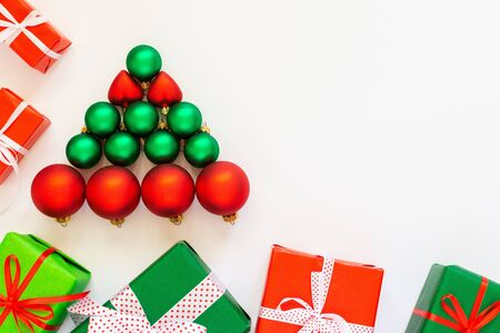 Holiday background with a decorative tree of red and green Christmas balls, gift boxes on a white background , flat lay, top view, copy space