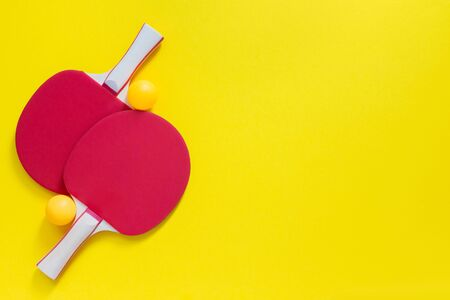 Red tennis rackets and orange balls isolated on a yellow background, sport equipment for table tennis