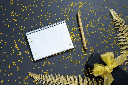 Festive background with gold decorations , shiny golden fern leaves and gift box on a black background with glitter gold stars ,open spiral notepad and pen, flat lay, top view