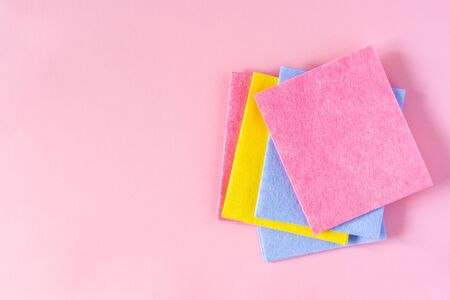 Multi-colored cloths on pink background, housekeeping and cleaning concept
