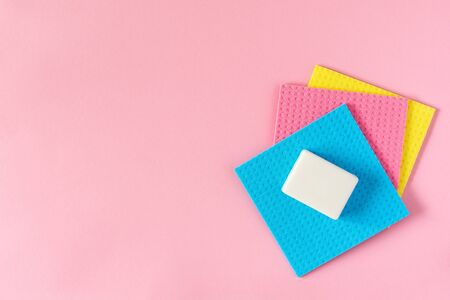 Multi-colored cloths and soap on pink background