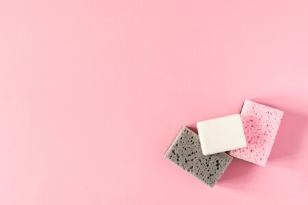 Multi-colored cleaning sponges with soap on a pink background, housekeeping and cleaning concept