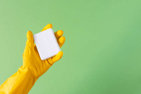 Hand in a yellow rubber glove with soap on a green background