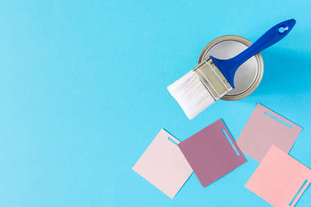 Can of white paint with brush on blue background, selection of palette for painting, sample color catalog, top view Stockfoto