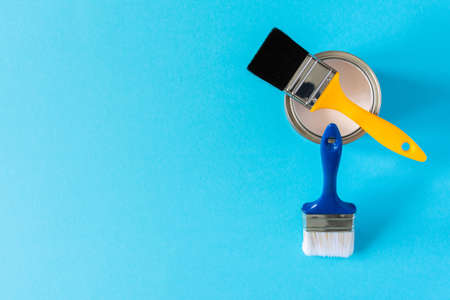 Can of white paint with brushes on a blue background, painting, top view