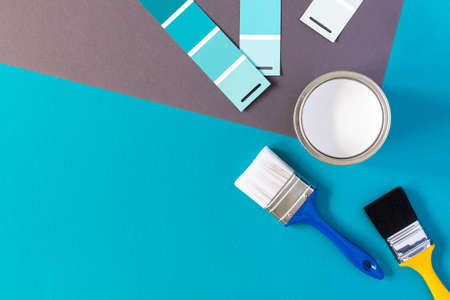 Can of white paint with brushes on colorful background, selection of palette for painting, sample color catalog, top view