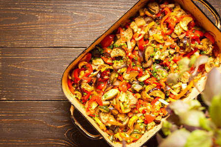 Stewed vegetables in an bowl, eggplant with zucchini and tomatoes, sweet and hot peppers and spices, mixing of Ratatouille ingredients in a bowl