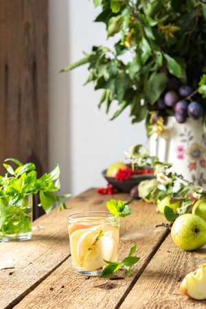 Autumn apple drink, apple slices with juice and mint in a glass on a wooden table, leaves in a vase, morning in the village, rustic concept Reklamní fotografie