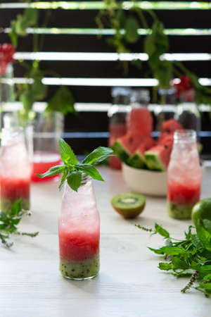 Cold refreshing watermelon juice, watermelon with kiwi and ice in bottles, fruit smoothie on wooden background Reklamní fotografie