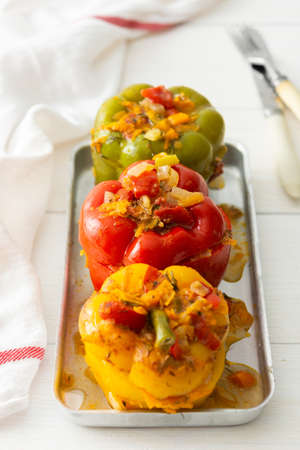 Meat and rice stuffed multicolored bell peppers with hats and vegetables closeup Фото со стока