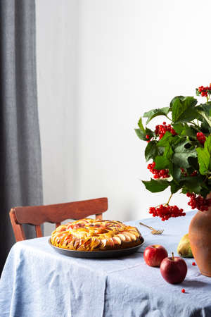 Delicious apple pie, home interior, table with blue tablecloth, clay vase with viburnum and fruits Stock fotó