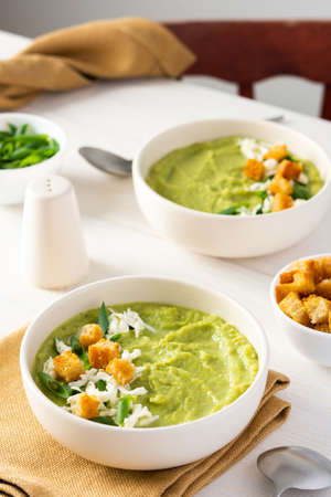 Healthy delicious broccoli and cucumber cream puree soup with mozzarella, green onions and croutons, bowl of soup on a white table Standard-Bild