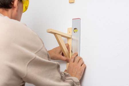 A man hangs a shelf in an apartment on a white wall, a worker checks the evenness of the shelf with a spint level