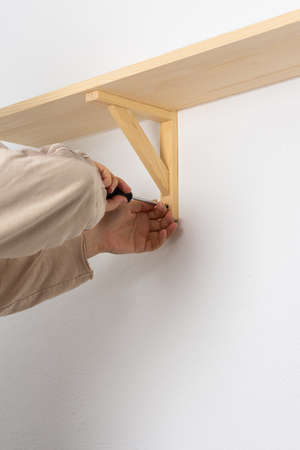 A man hangs a shelf in an apartment on a white wall, a worker fixes screws on a shelf corner with a screwdriver