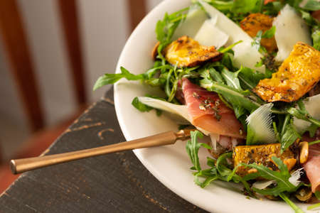 Light autumn salad with arugula, baked pumpkin, prosciutto and young parmesan, a plate of salad on a wooden table