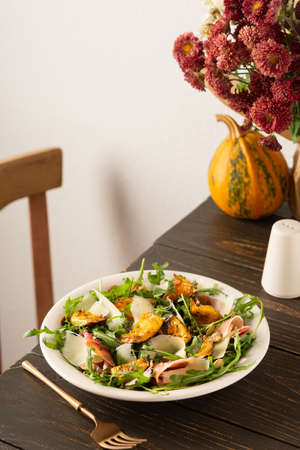 Light autumn salad with arugula, baked pumpkin, prosciutto and young parmesan, a plate of salad on a wooden table, chrysanthemums in a vase Banque d'images