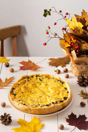 Quiche pie with mushrooms and cheese, autumn background with fallen maple and oak leaves, pine cones, rose hips and hazelnuts