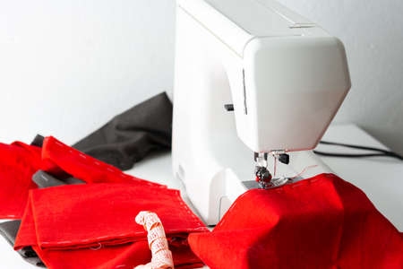 Modern sewing machine with red and gray fabric, measuring tape , cutting and sewing at home, home leisure and hobby