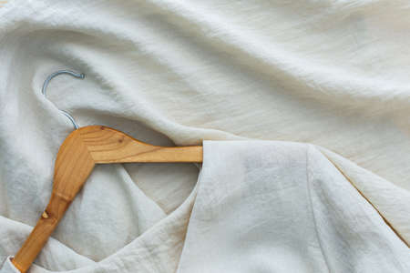 Wooden hanger with linen dress , fashion and consumption concept