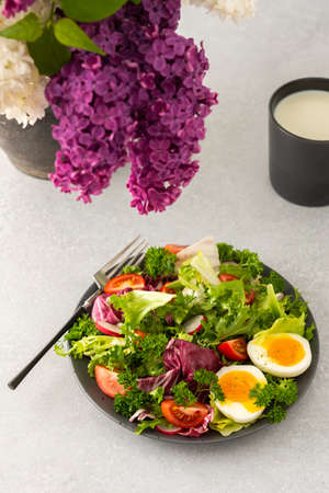 Delicious healthy breakfast, mix salad with tomatoes and radishes, boiled egg and a mug with milk, vase with lilacs