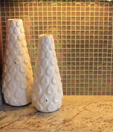 countertops: White vases against glass tiles in kitchen Stock Photo