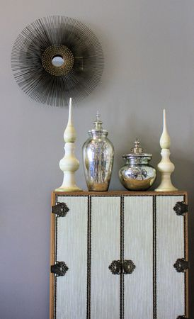 textured wall: Beautiful cabinet with vases and modern wall hanging Stock Photo