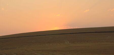 over the hill: Campo de trigo y la puesta de sol sobre la colina Foto de archivo
