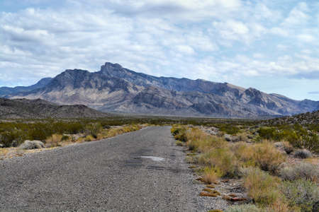 Gravel road in desert with mountain in background