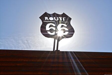 Route 66 sign with the sun shining throught the sign