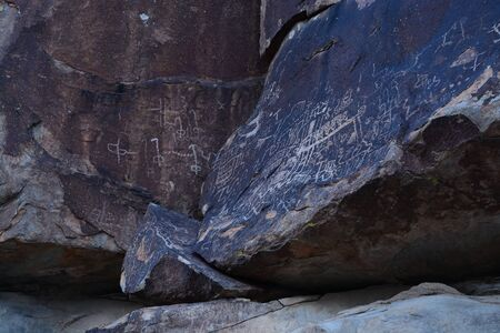 Petroglyphs in the shadows of rocks Stock Photo - 99084860