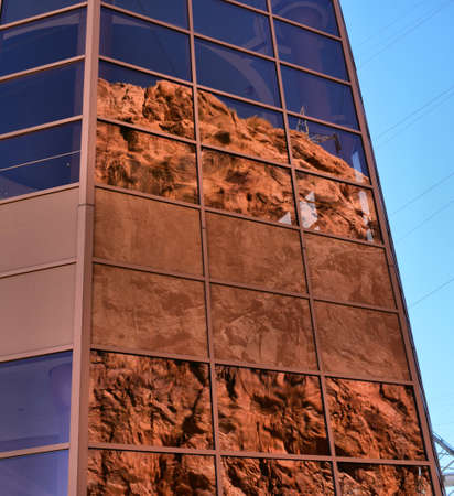 Reflections of red rock against windows of highrise