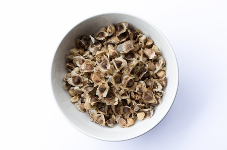 drumstick tree: Moringa seeds dry in white bowl and wooden spoon