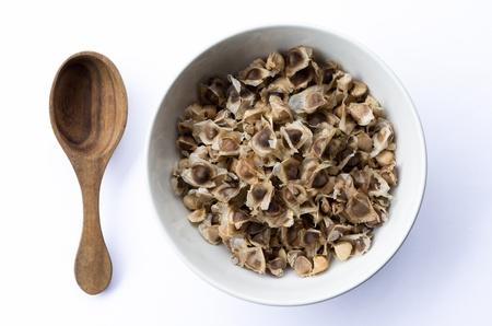 Moringa seeds dry in white bowl and wooden spoon photo