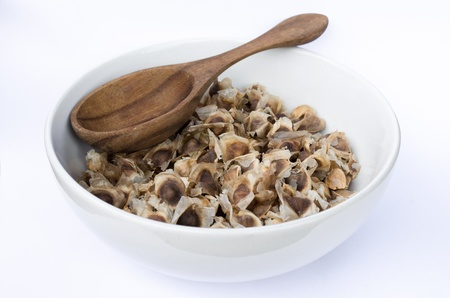 laxatives: Moringa seeds dry in white bowl and wooden spoon