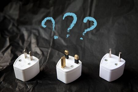 adapters: Choosing from various electric plug adapters. Traveling difficulties