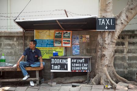 taxista tailandés espera para los clientes junto al anuncio. servicio de taxi de la calle Editorial