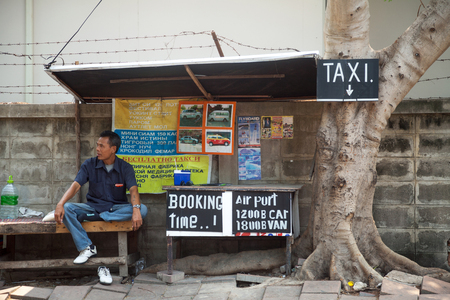 commercial tree service: Thai taxi driver waiting for customers next to advertisement. Street taxi service
