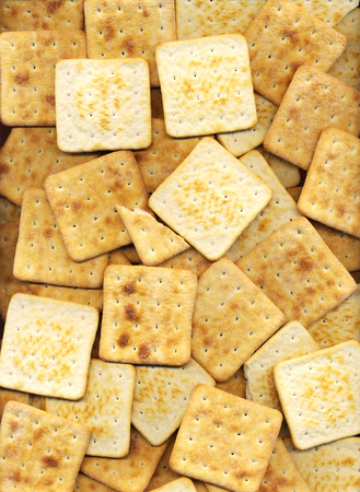 Graham: Pile of square salty crackers background. Many baked graham crackers pattern close-up