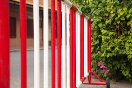 no entrance: Metal red and white safety barrier on a road. Stop sign railing against green bushes Stock Photo