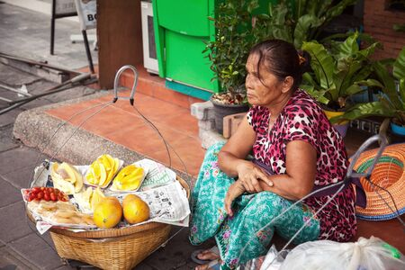 seller: Pattaya, Thailand - March 28, 2016:  Thai street vendor selling fruits from baskets. Food seller sitting on pavement