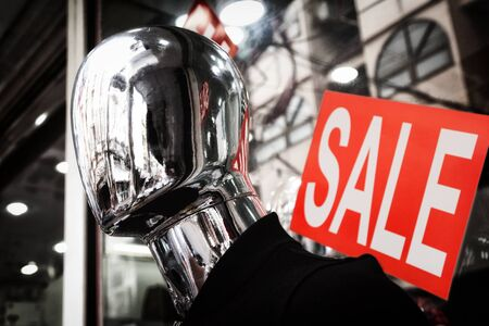 senseless: Faceless silver mannequin head dark close-up. Red sale sign