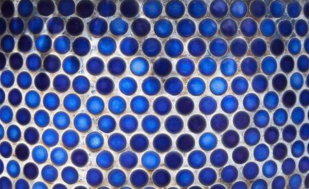 bathroom wall: Blue penny circular ceramic tiles background. Tiled indigo color bathroom wall