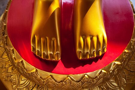painted toes: Golden feet on a red background vivid close-up. Asian shrine sculpture feet, nice and clean
