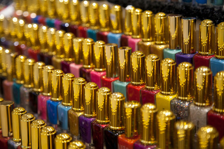 Many nail polish multicolor bottles arranged in rows background. A lot of different colors nail varnish in a shop display Фото со стока