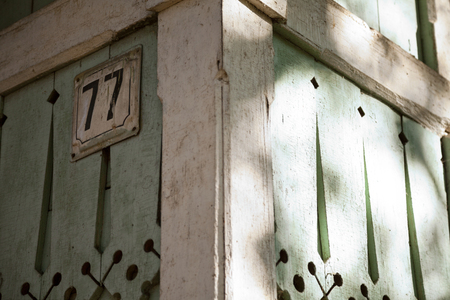 number plate: Traditional Russian wooden house with number plate close-up. Wood carved decorations on a green rustic building. Architectural detail