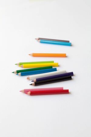 Bunch of fun mini colored pencils isolated on white. Group of cute small colorful wood pencils. Selective focus on the blue one
