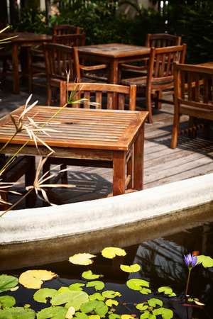 back yard pond: Outdoor cafe patio with old, shabby wooden tables and chairs in the sunlight. Pond with water lilies on a  romantic restaurant terrace