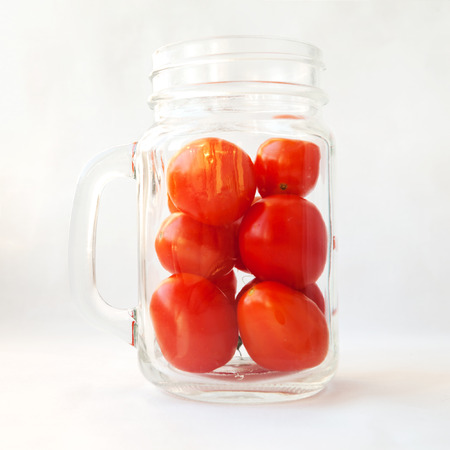 Tomato juice, drink, smoothie in a glass concept. Plum tomatoes in a transparent jar mug isolated on white. Many small fresh red vegetables in a cup Stock Photo