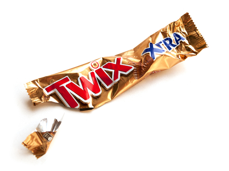 Twix Xtra chocolate bar empty crumpled wrapper isolated on white. Food packaging garbage