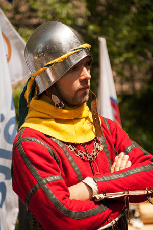 Khabarovsk, Russia - June 11, 2017: Middle ages period costume at knight tournament. Young man wearing metal helmet and red cotehardie at historical medieval reenactment